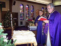 Father David reading the prayers of the blessing.  Assisting is the parish's Deacon Robert Conjelko
